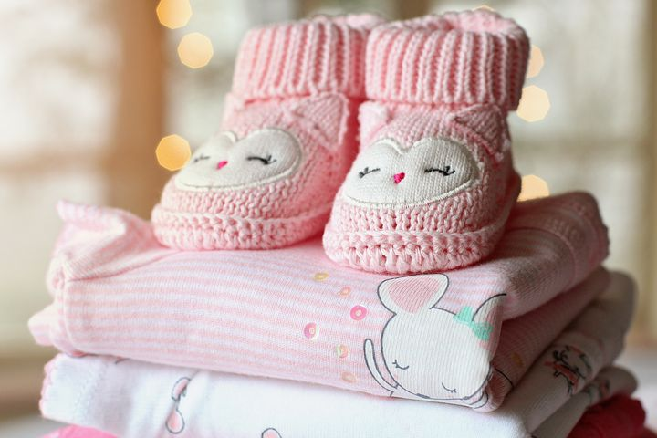 Pink baby booties on stack of folded blankets.
