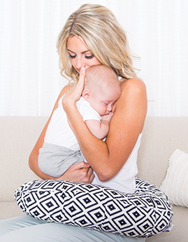 Woman holds baby with nursing pillow.