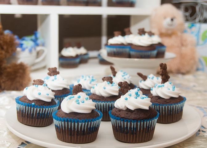 Chocolate cupcakes with white frosting and blue sprinkles.