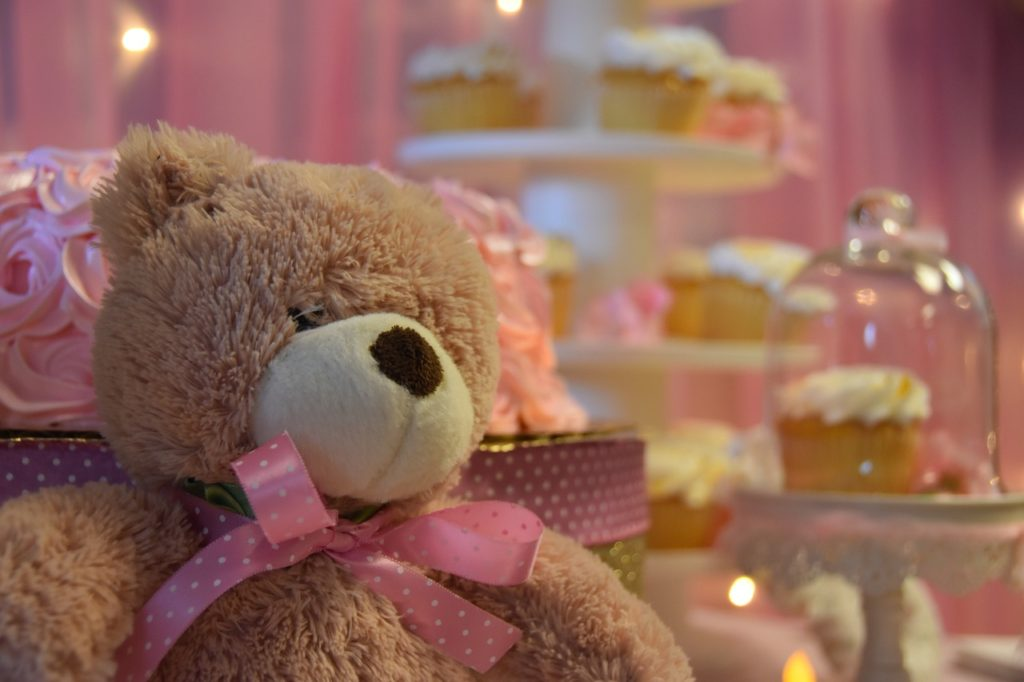 Teddy bear with pink bow at baby shower.