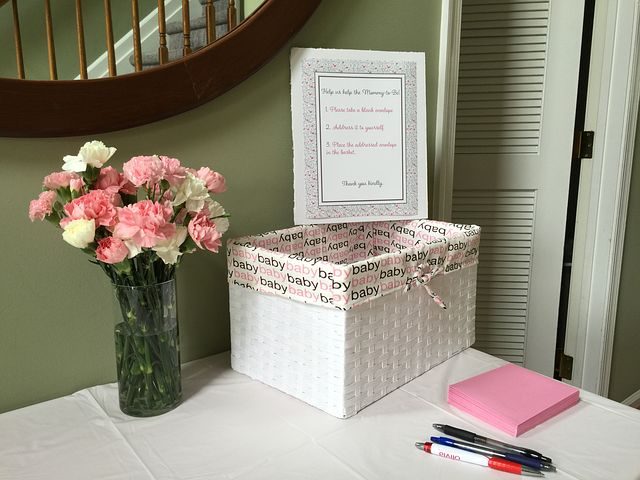 Baby shower guest book next to bouquet of flowers.
