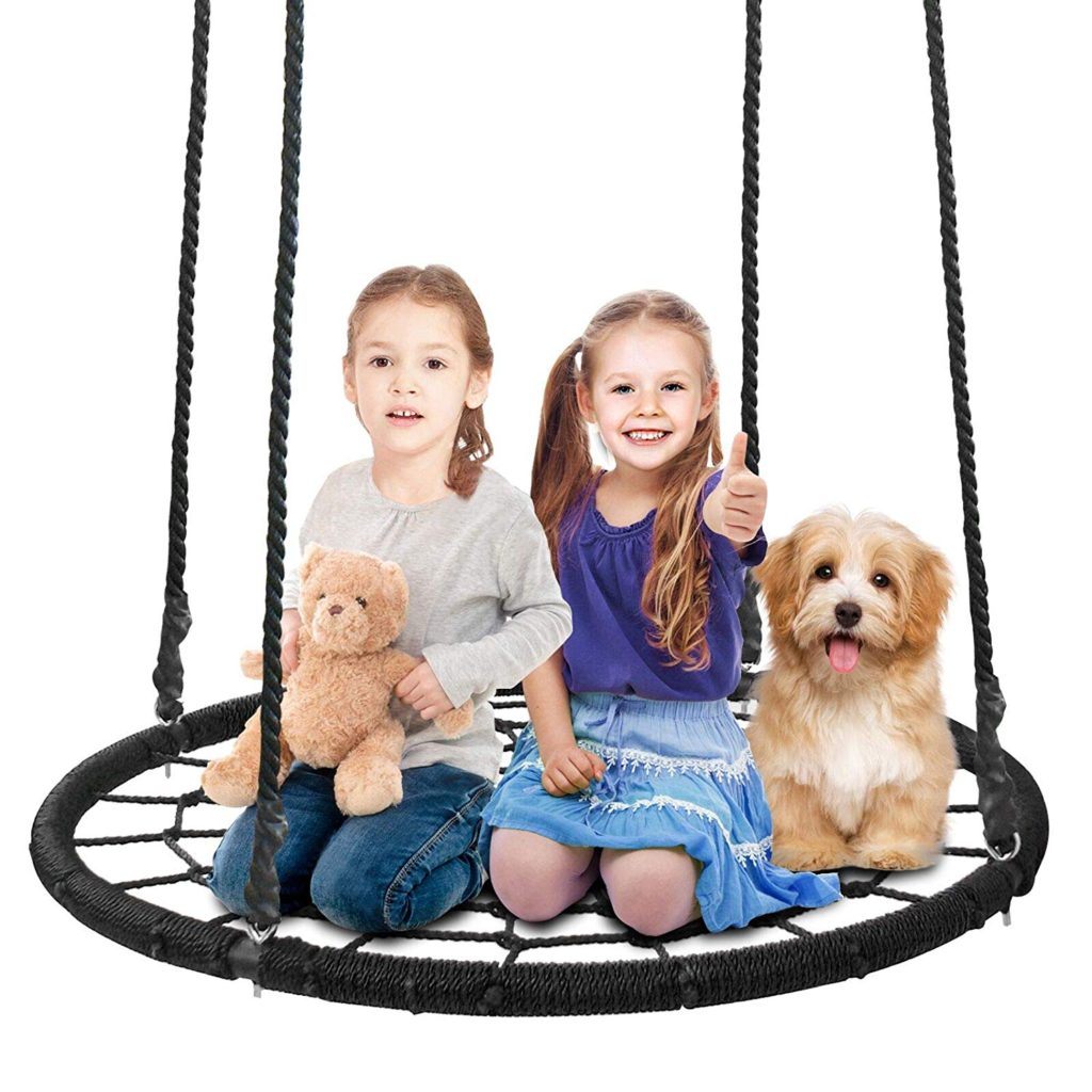 Children play on spider web tree swing with stuffed animals.