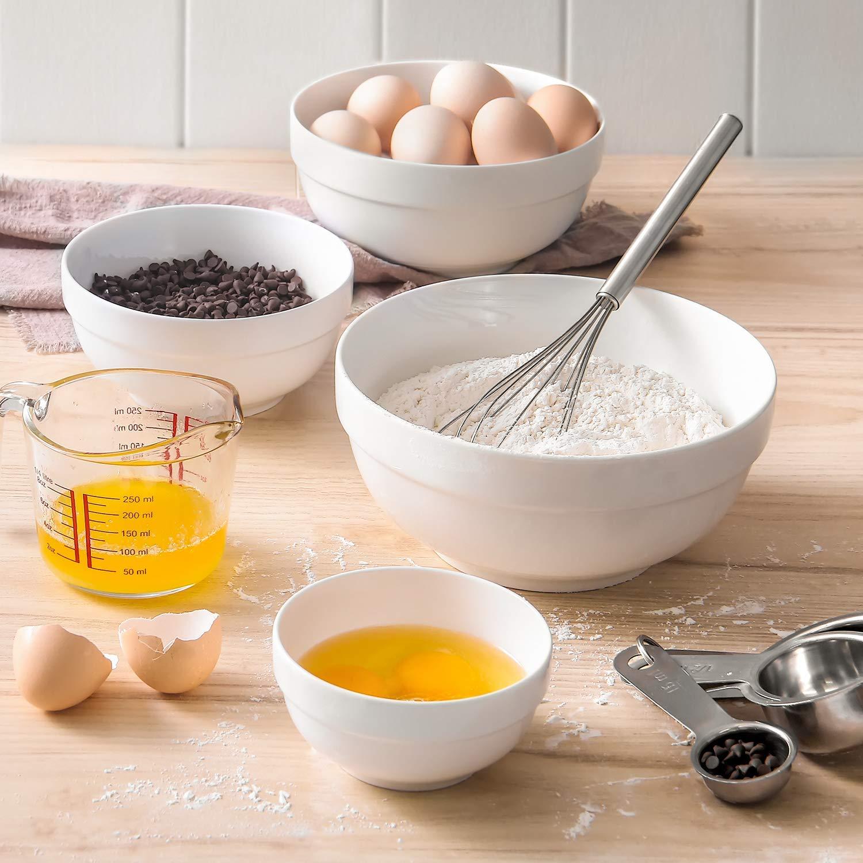 White mixing bowls with various baking ingredients.