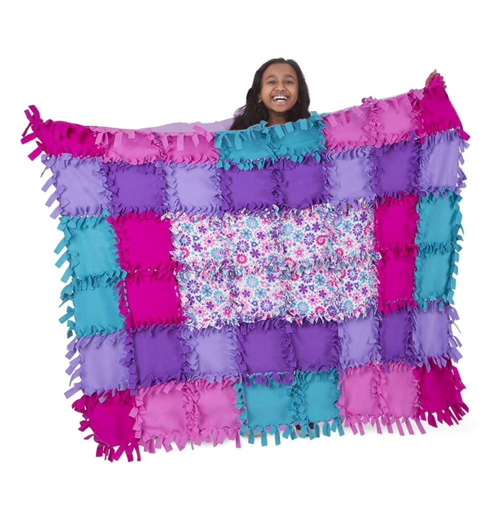 Young girl models quilt from no sew fleece quilt kit.