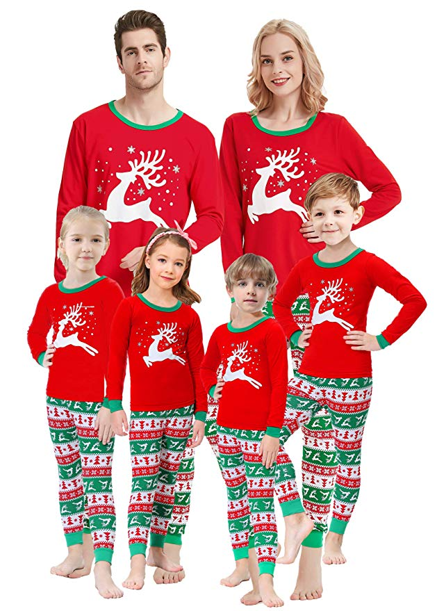 Family models Christmas sleepwear with reindeer design and red, green and white striped pants.