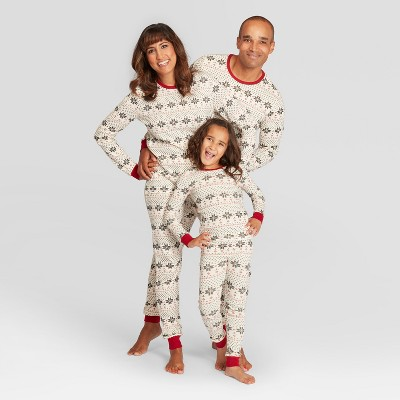 Parents and child model pajamas that match for Christmas.
