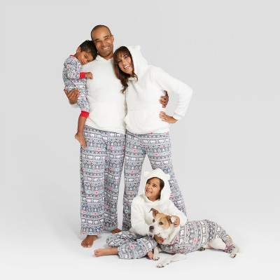 Family with dog in matching gray, red and white pajamas.