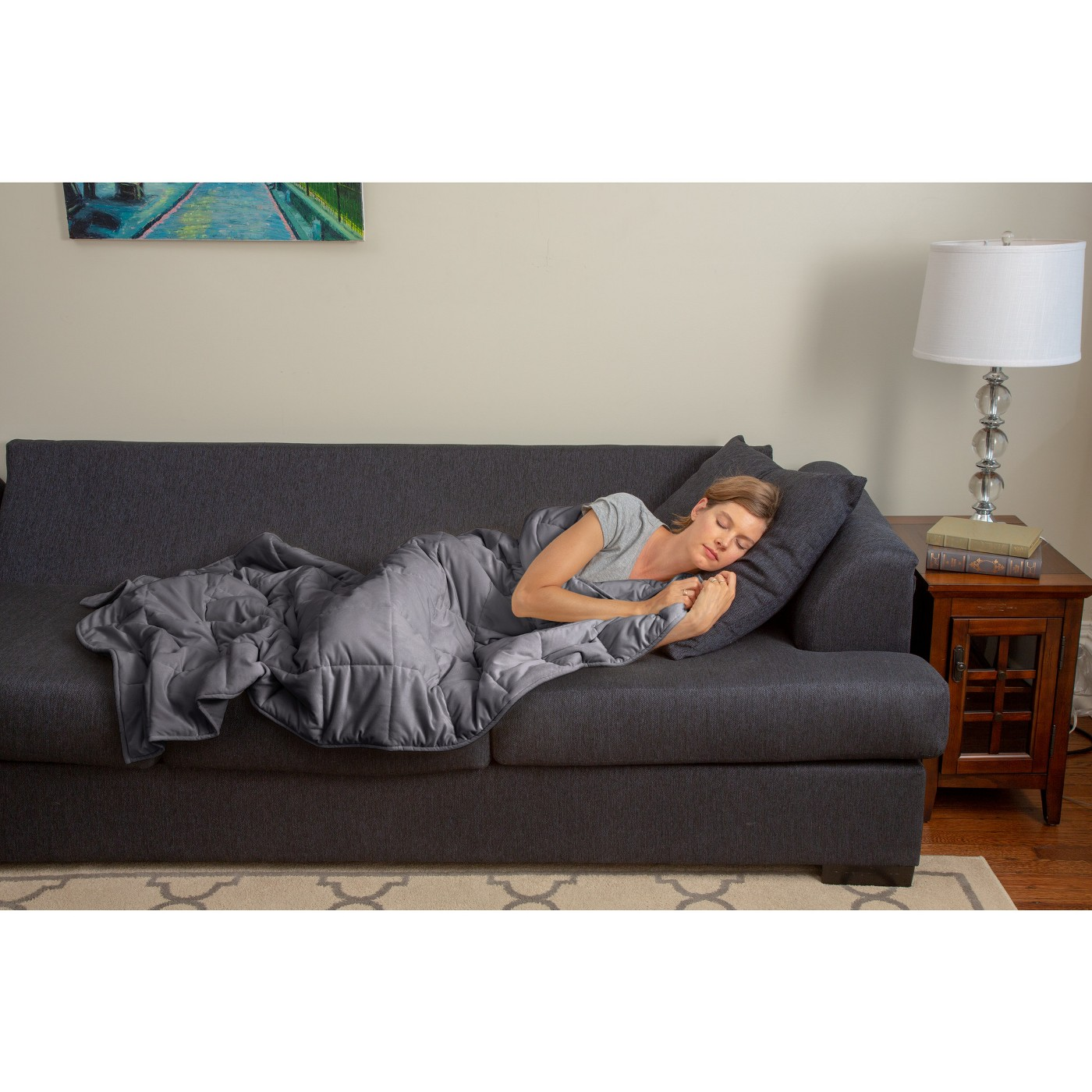 Woman lies on couch with gray weighted blanket.