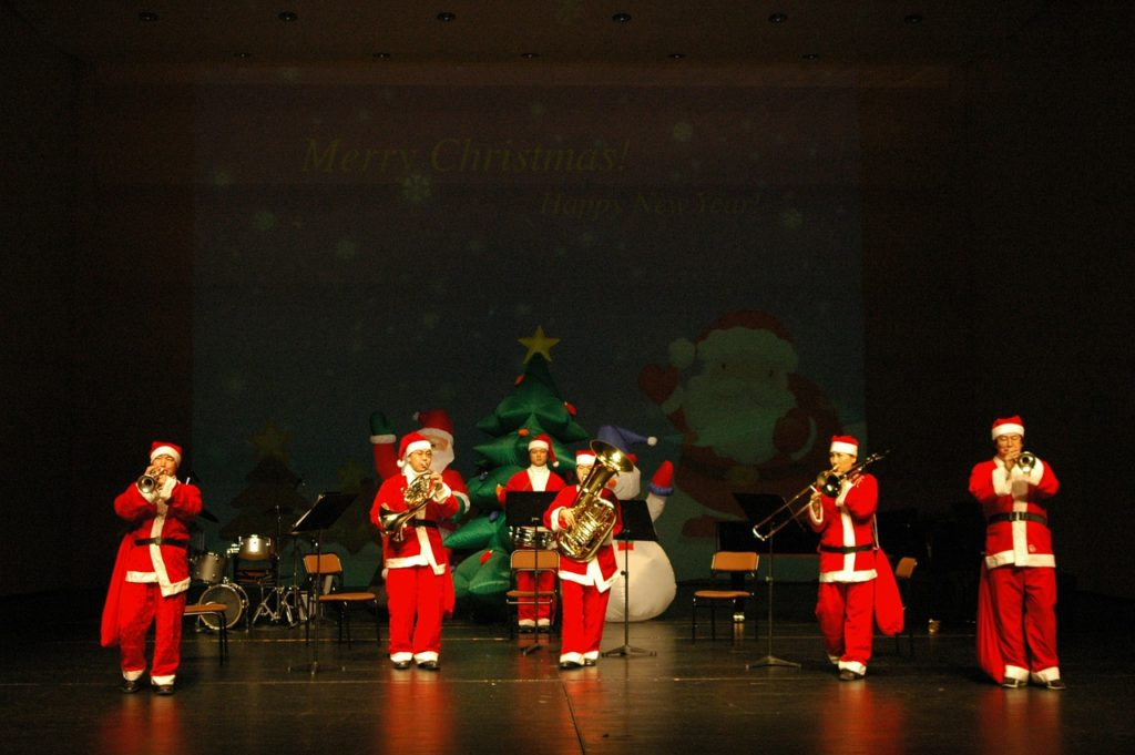 Musicians in Santa outfits for Christmas concert.