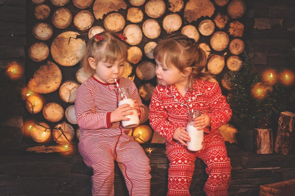 Toddler girls and red and white Christmas pajamas, drinking milk.