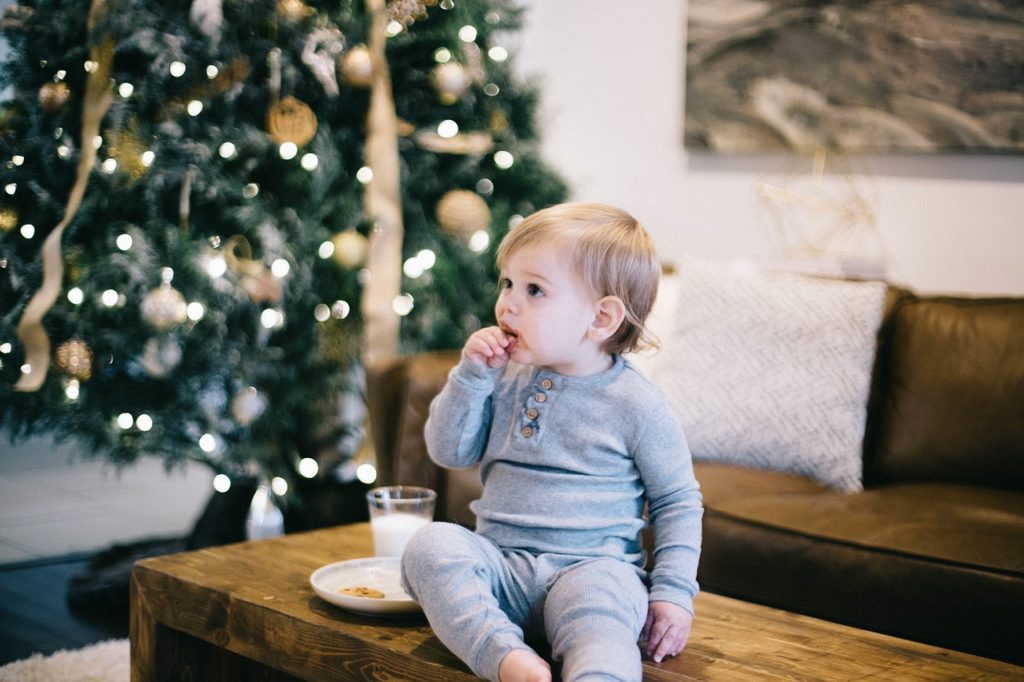 Baby girl sits in front of Christmas tree with cookies and milk.