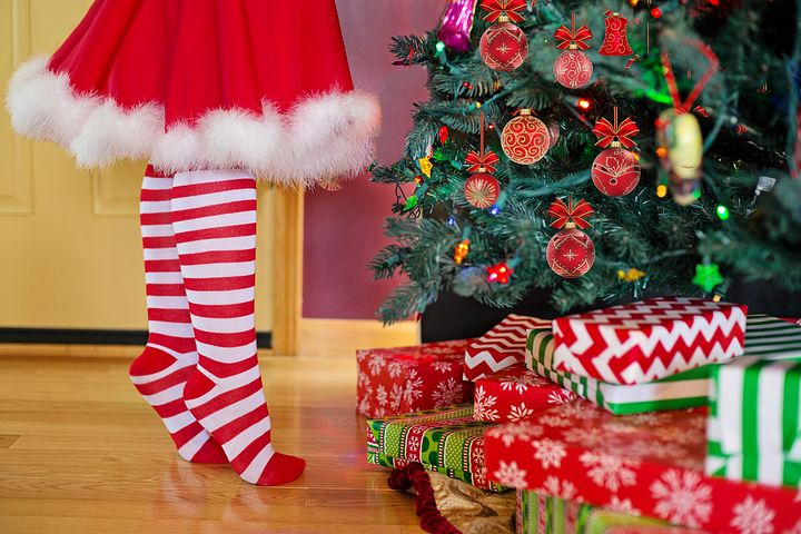 Person in candy cane striped stocking stands on tiptoes in front of Christmas tree with presents.