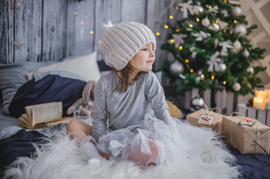 Little girl in beanie and white tutu sits in front of Christmas tree.