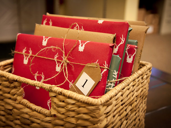 25 books wrapped for Christmas in basket.