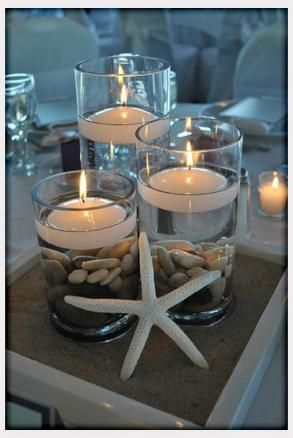 Glass jars with sea rocks, floating candles and starfish for baby shower centerpieces.