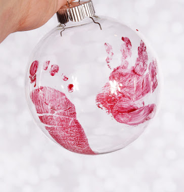 Clear Christmas ornament with baby\'s hand and foot print.