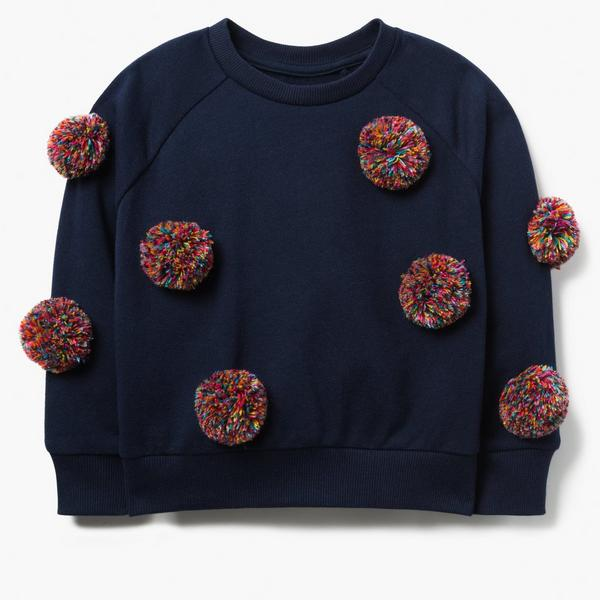 Dark blue sweater, dotted with colorful pompom detail.