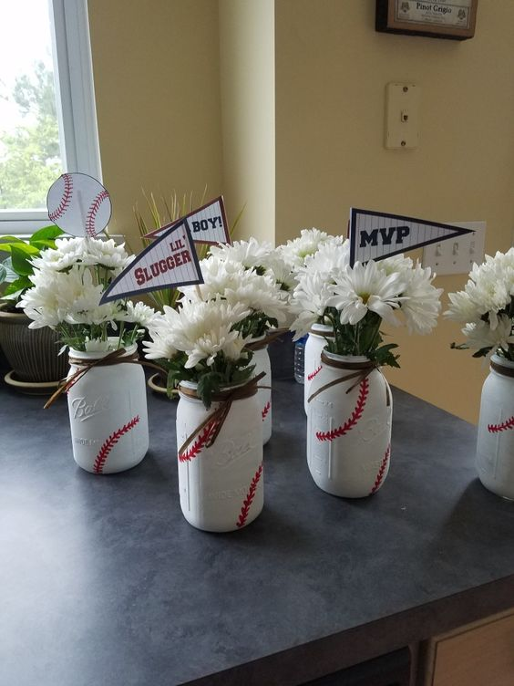 Mason jar baseball centerpieces with flowers and slogan flags.