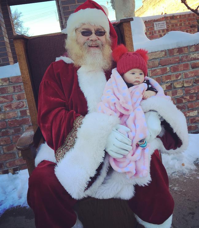Baby sits on Santa\'s lap.