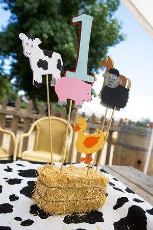 Farm baby shower centerpiece with mini hay bale and animal figures.