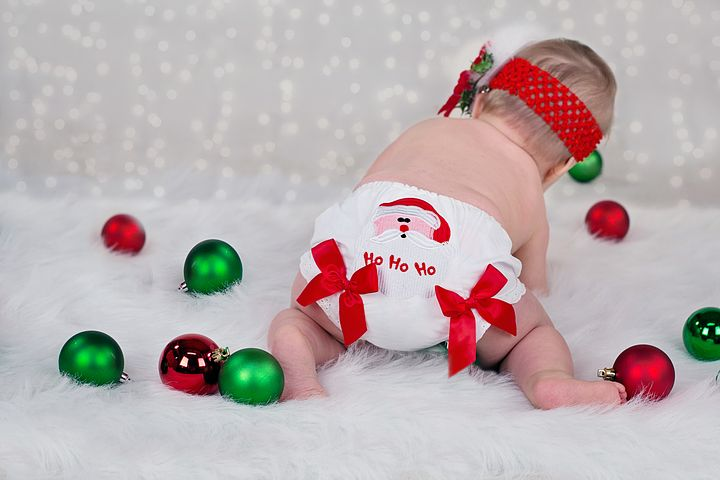 Newborn baby surrounded by Christmas ornaments.