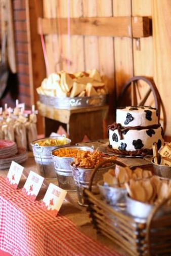 Farm themed baby shower food table with metal tin containers and cow print cake.