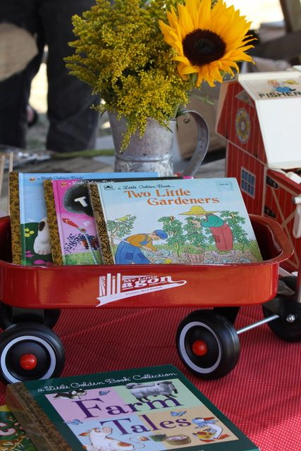 Farm themed baby shower decorations with wagon and children\'s books.