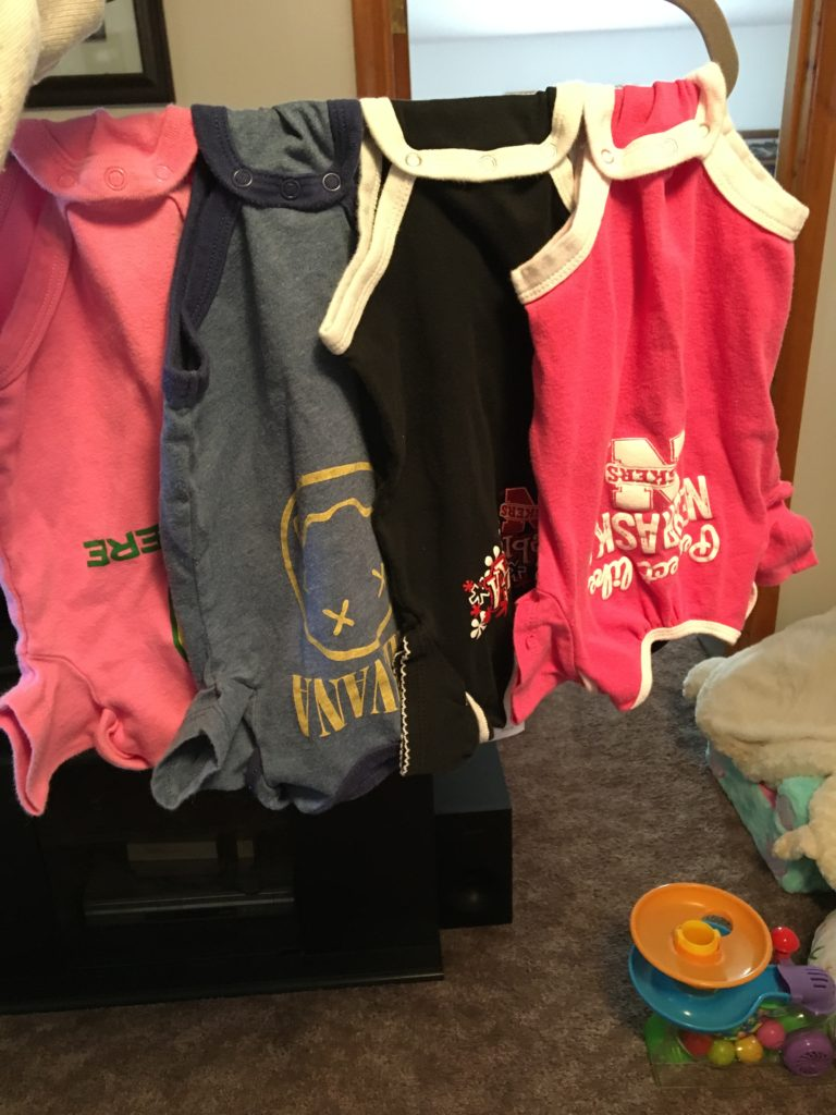 Several baby onesies hanging on a hanger.