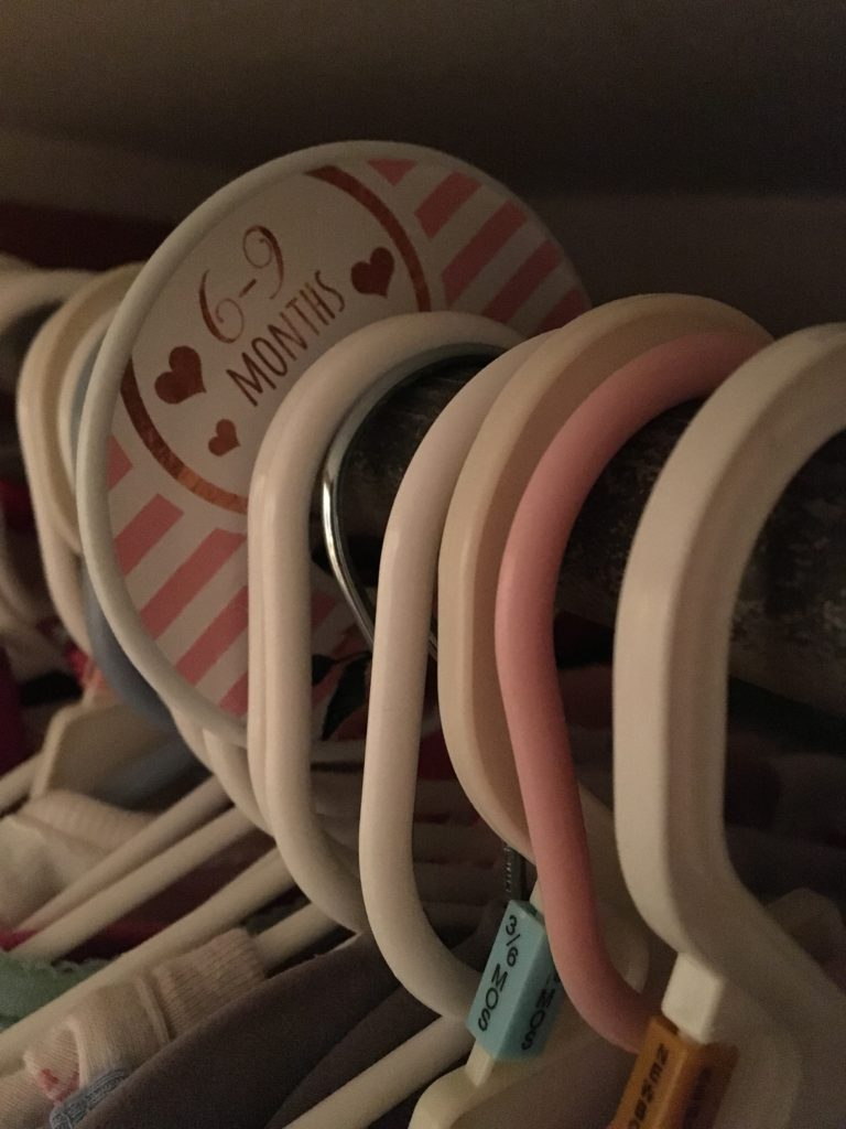 Closet dividers separate baby clothing by month.