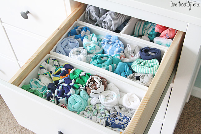 Several rolled up baby clothing items in organized drawer.