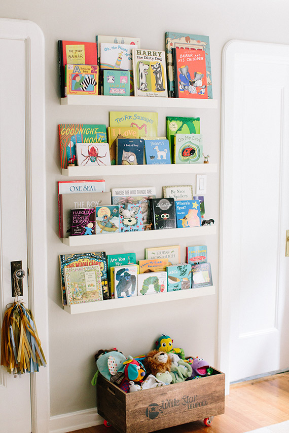 White, floating shelves filled with children\'s books.