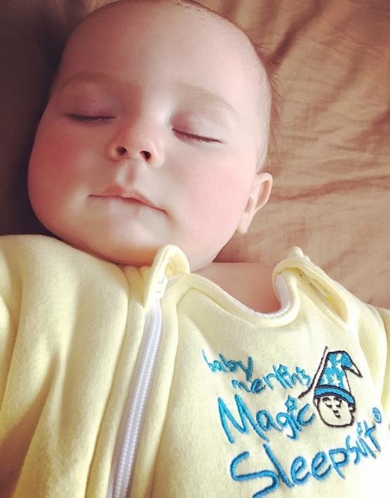 Baby sleeping in yellow baby suit.