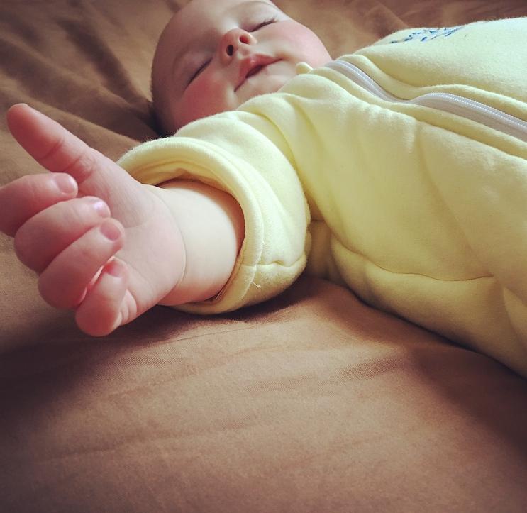 Baby sleeping in sleep suit.