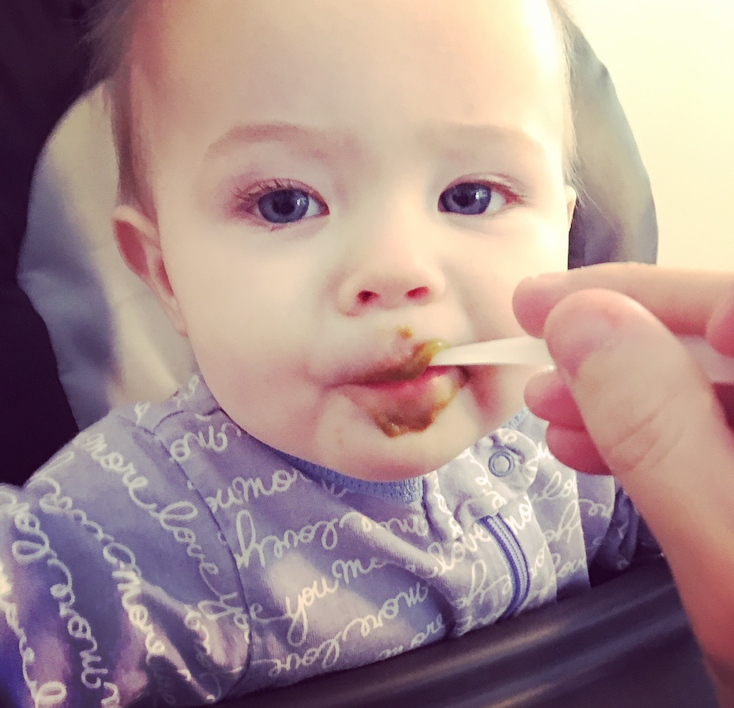 Baby is fed baby food in high chair.
