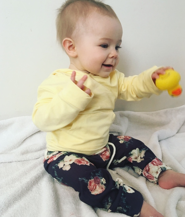 Baby girl wears outfit from Amazon and plays with toy duck.