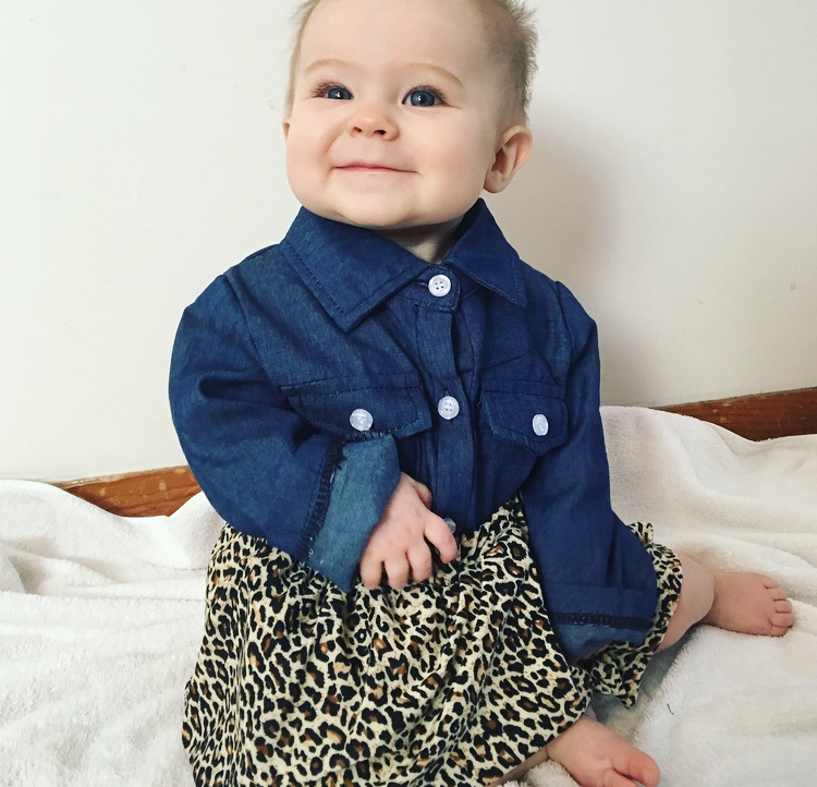 Baby girl wears leopard print skirt with matching bow and denim top.