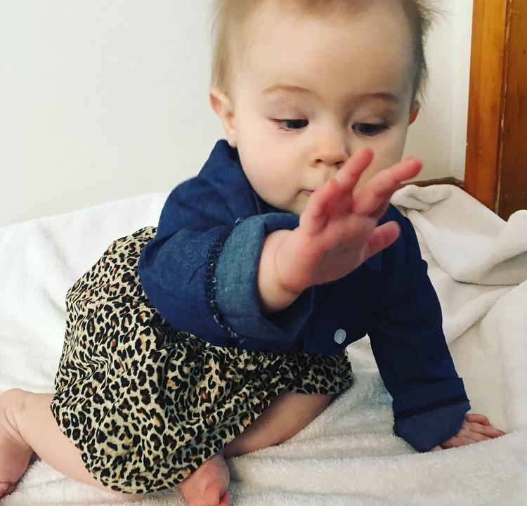 Little girl in denim top and leopard skirt.