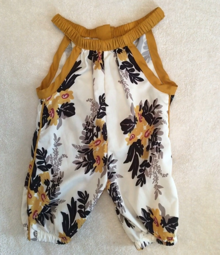 White romper with gold and blue floral print for little girl.