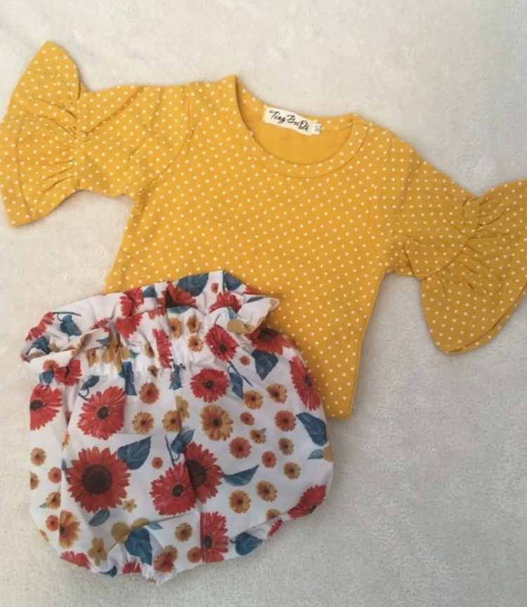 Yellow gold top with white polka dots and matching flowery shorts for baby girl outfit.