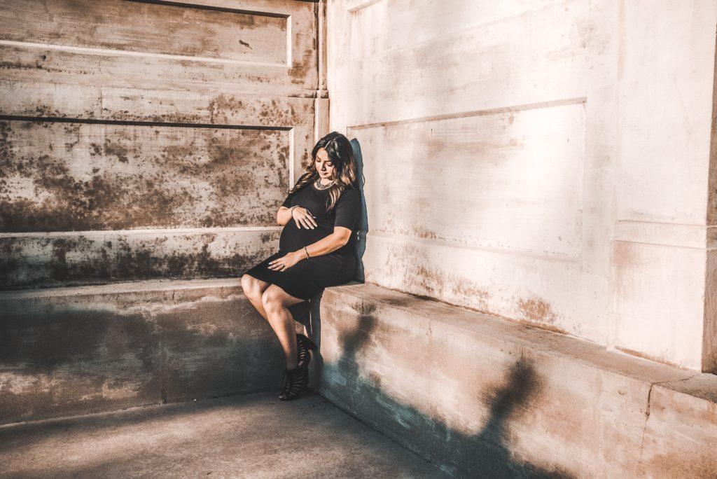 Pregnant woman sits on concrete ledge.