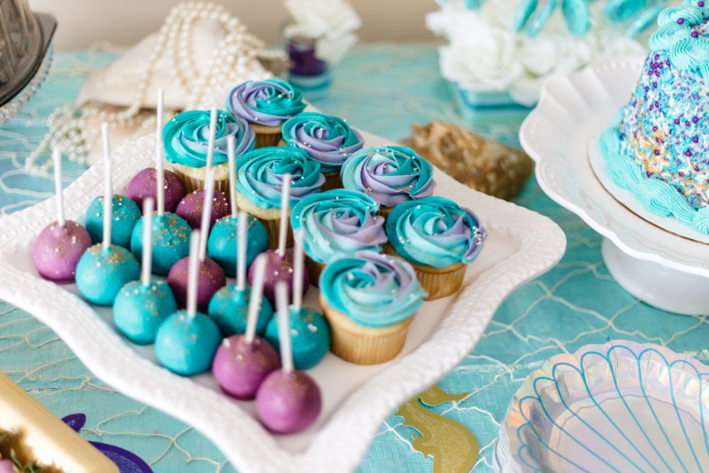 Purple and blue cupcakes and cupcake bites on party table.