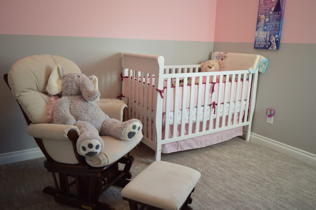 Pink and gray nursery with crib and glider.