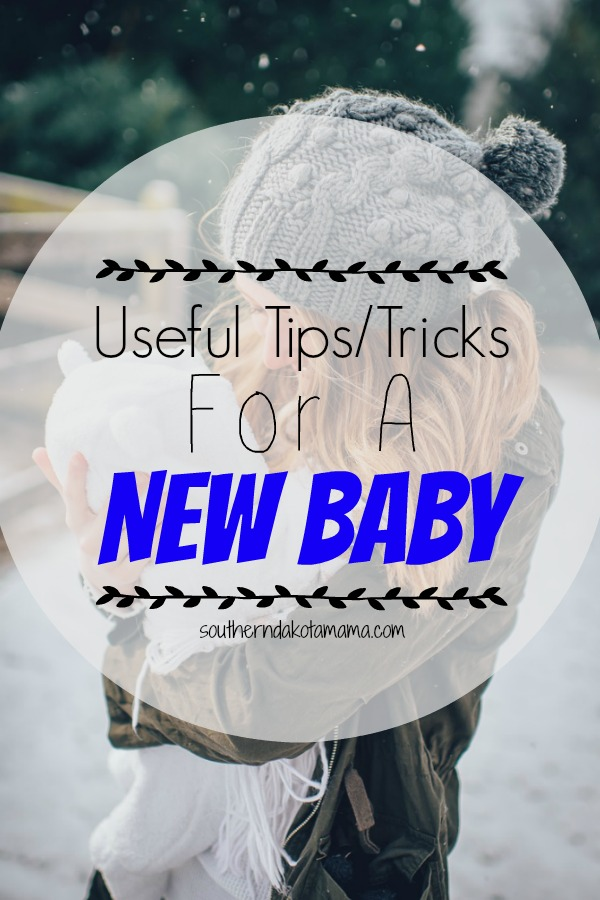 Pinterest graphic with text for Useful Tips/Tricks for a New Baby and mother holding baby outside.