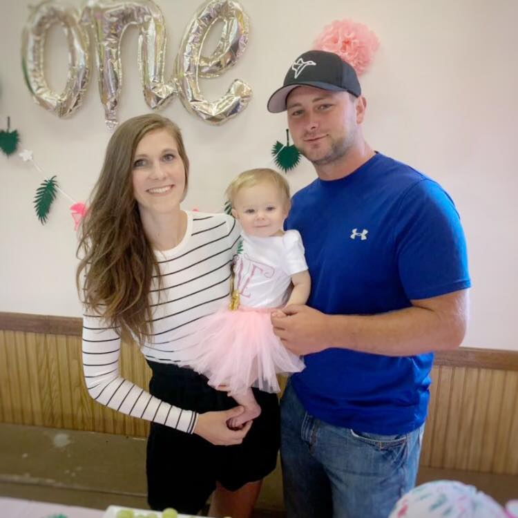 Couple holds baby at one year old birthday party.