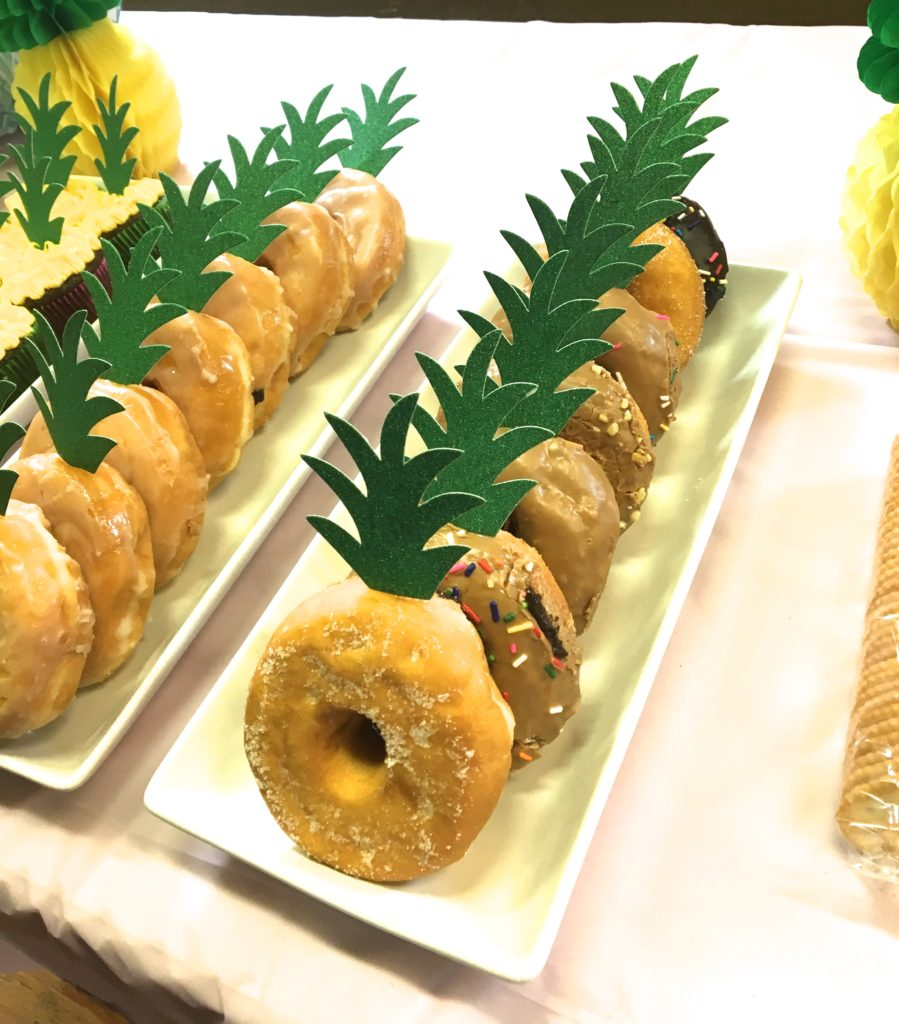 Donuts topped with faux pineapple leaves.