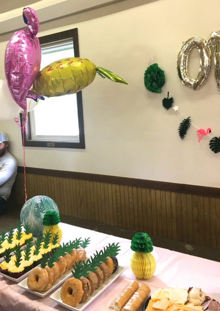 Close up of birthday party food table with tropical balloons and banner.