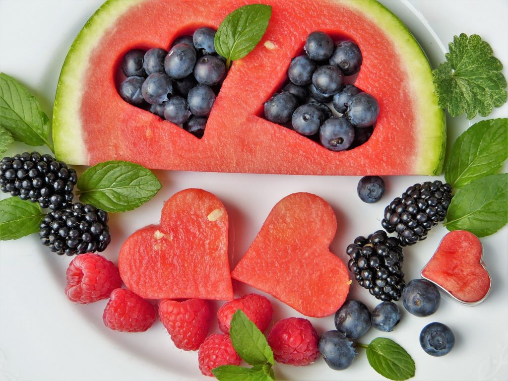 Watermelon with heart-shaped cut outs and berries.