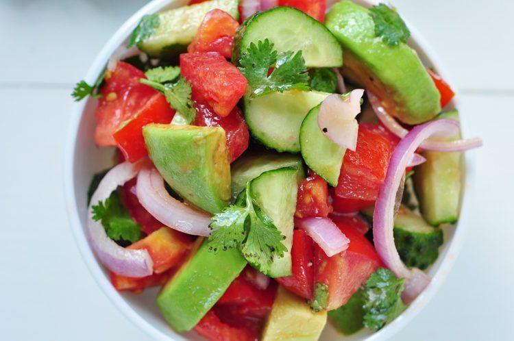 Healthy avocado, cucumber, tomato and cilantro salad.