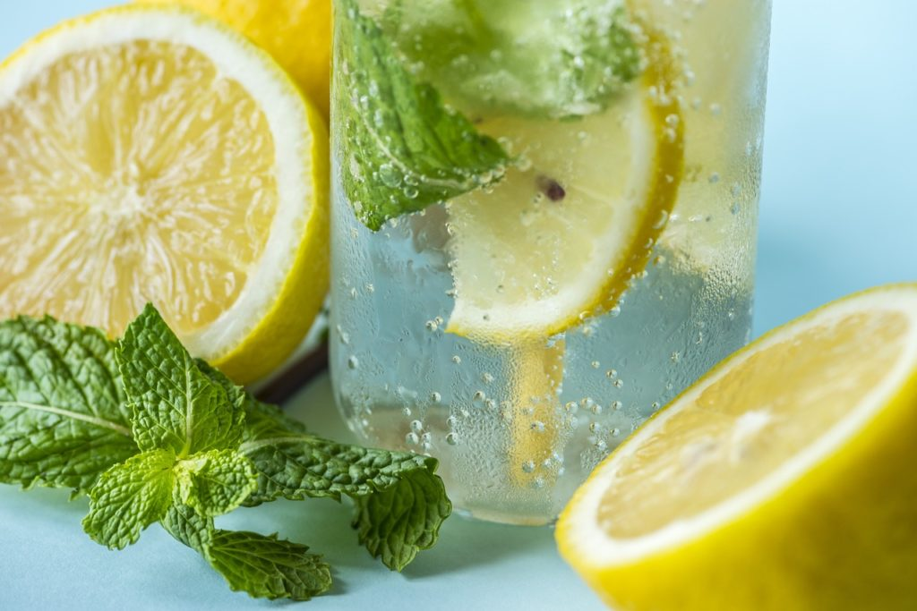 Beverage with lemon slices and mint leaves.