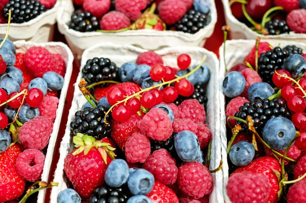 Variety of berries in white baskets.
